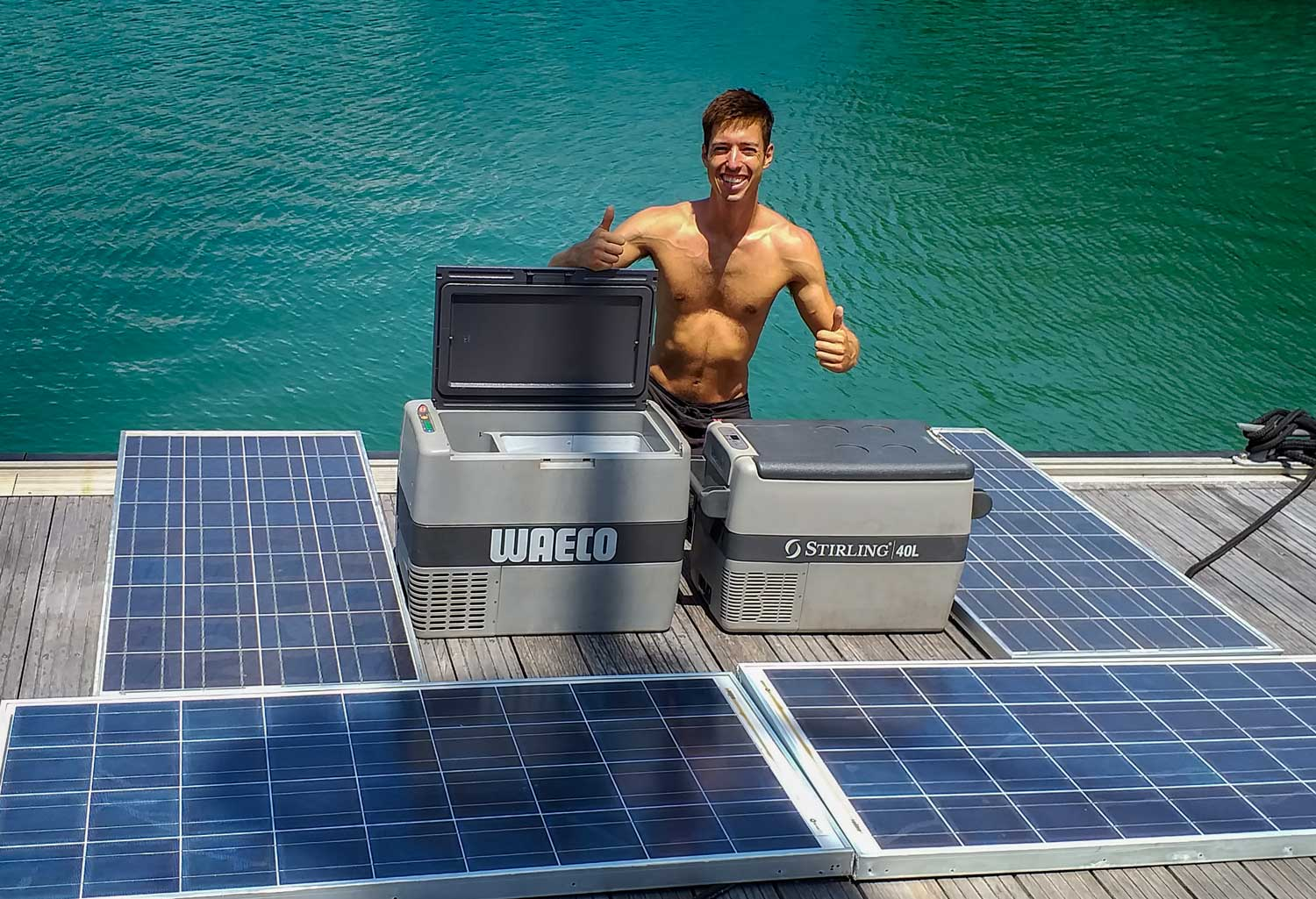 Canadian volunteer crew member Sam displays two portable solar powered cold boxes with four of the solar panels we acquired.